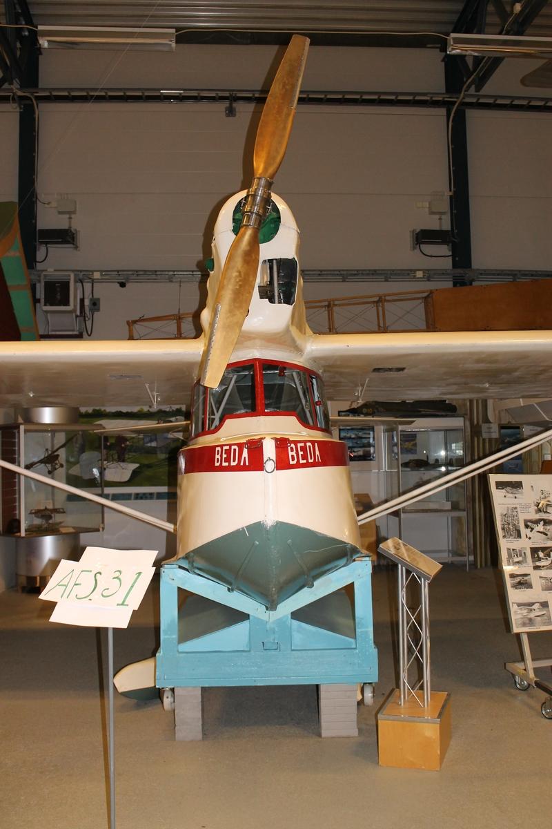 """Flygbåt kallad """"Beda"""". Tillverkad i trä, vitmålad med röd dekor. Urtag i kropp och vingar täckta av glaspaneler gör det möjligt att inspektera roderlinor och bryttrissor. Märkning i vitt på båda sidor om nossektionen: """"BEDA"""". Den innehåller delar från Klemm Kl 35 SE-BGX, däribland styrsystem inklusive pedalställ och stålrörstomme i kabinen och eventuellt enstaka delar från en Zlin XII. Propellern och stabilisatorn är omställbara. Flygbåten är monterad på en kroppsvagga, under vilken de båda stödflottörerna finns. Stöttor för att montera dessa stödflottörer under respektive vingspets saknas."""