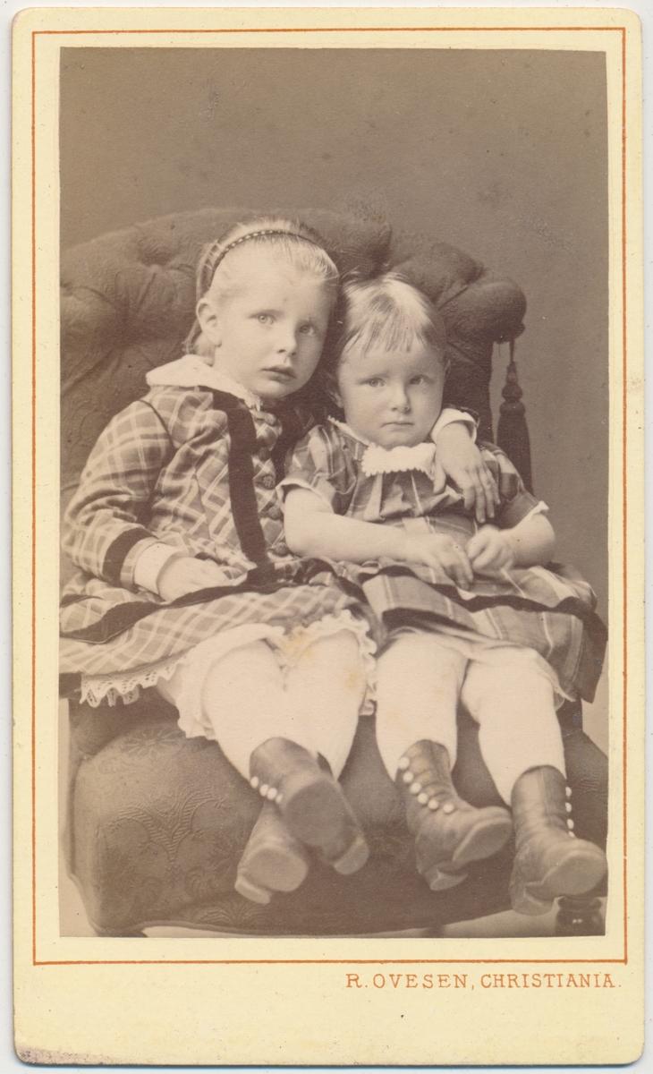 Skancke To små jenter sittende i stol, ukjente