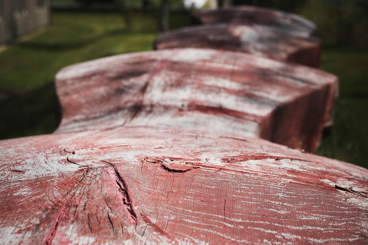 Sitteskulptur i heltre med rød fargesetting.