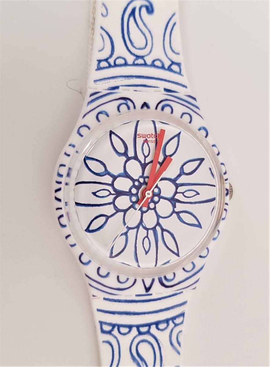 Armbåndsur : hvit bunn farge med blå dekor. Urskiva har en stilisert blå blomst, røde visere med en blank, metall sekundviser.  Blomstens kronblader viser hel time, de 4 største viser hvert kvarter, dvs. peker mot kl 3, 6, 9 og 12. Reima er av plast og er dekorert med blå stiliserte blomster, bladranker og paisleyformer. Spenne i mørk kongeblå plast. På baksiden er metallokk for ilegg av batteri.