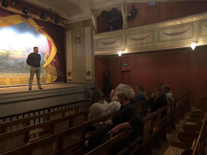 Viser formidler på teaterscenen som snakker til vidergående elever som sitter i salen