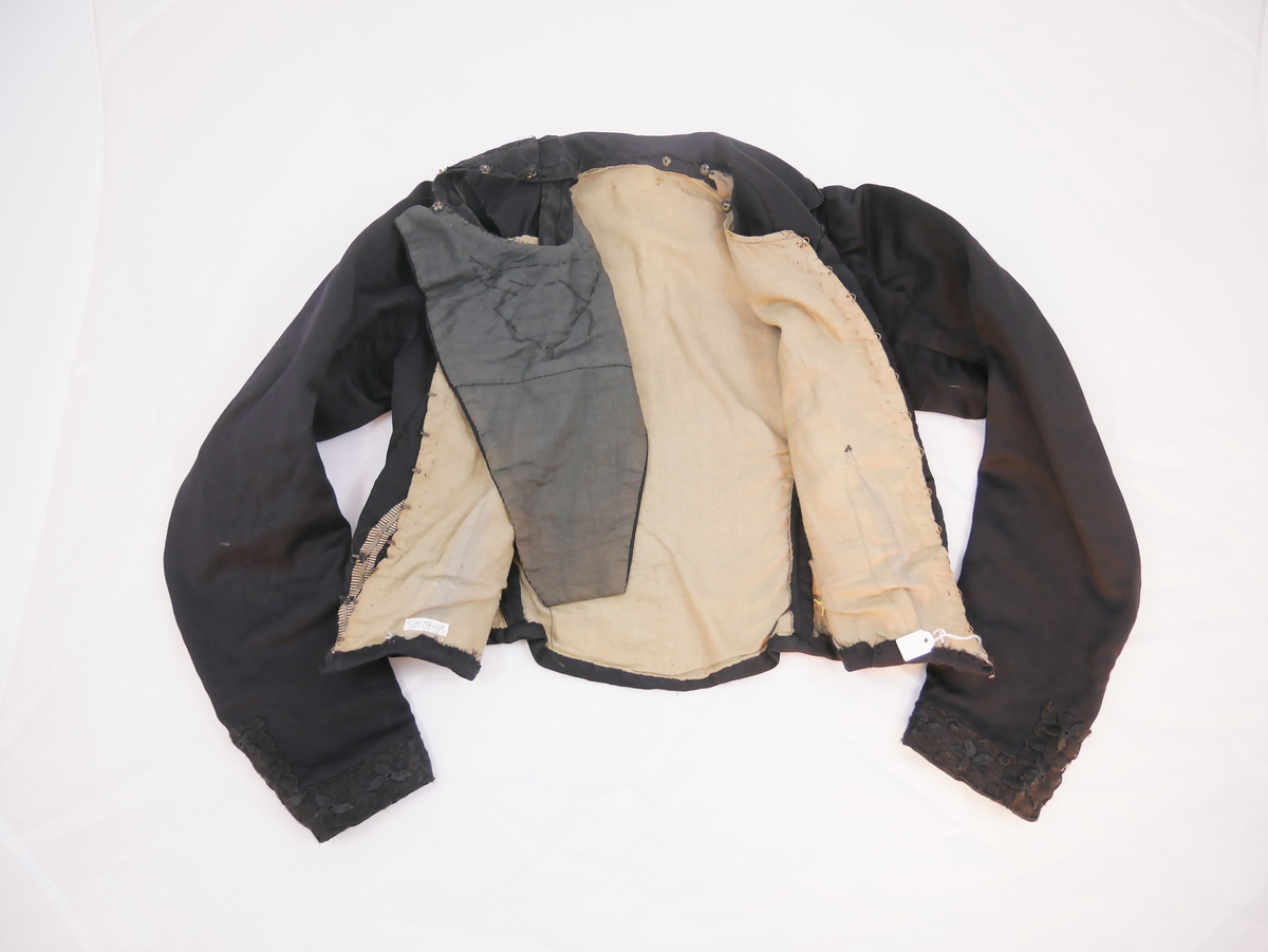 """Kort overdel som høyrer saman med skjørt SUM.09484 til kjole (""""bykjole""""). Forma som jakke med  stor krage og v-opning over falsk bluse  med brei halslinning .Trange ermer med lang splitt m/trykknappar framme. Store legg på begge framdelene. Linningar, kantar og den falske blusen er dekorerte med tunne svarte florblonder. Föret er luka med 12 sett hekter og hemper. Skjørtet har lnr. SUM.09484"""
