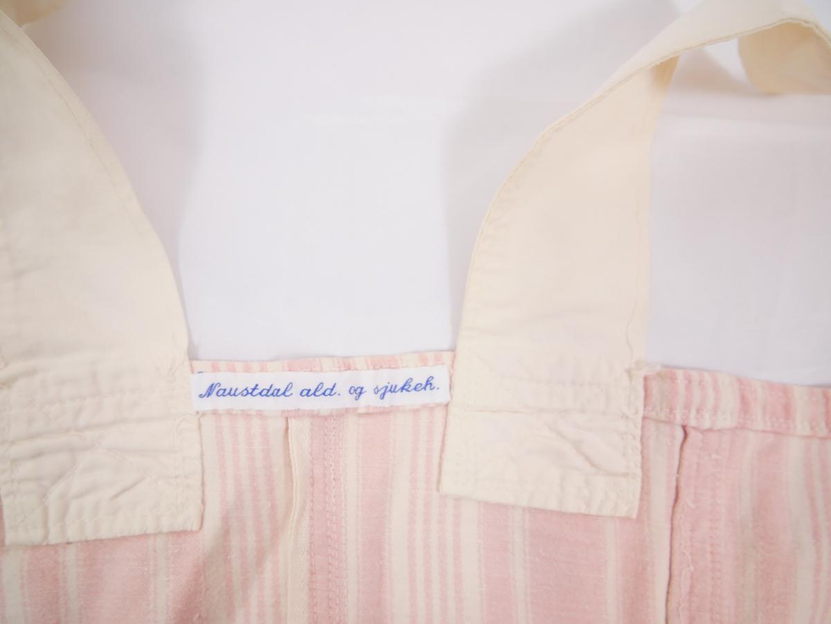 Underliv i bomull med diagonalt stripete mønster i hvitt og rosa. Stropper i hvitt. To hvite knapper nederst på hver side. 14 metallhekter sydd på innsiden av livet, 7 på hver side.