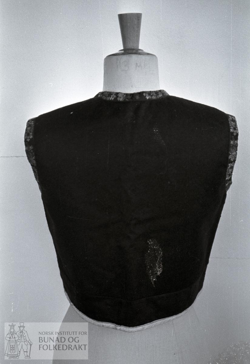 Nordhordlandsmessa 1974 - - - - - Blått kypertvevd  vadmål, pressa. Skjøtt bak, framme og i sidene. Kanta med svarte, rosa silkeband i flere fargar 1,8 cm breitt. Skuldersaum, sidesaumar langt bak. Fôra med tynt bomullslerret. Kvart stykke fôra for seg. Innsydd i sidene. Eit innsnitt på kvar side framme. Maskinsydd. H. midt bak 42,5 cm. Br. skulder 13,5 cm. H. under erme: 21 cm. Vidde 16 -> 62 -> 79 cm. H. skulder framme 42 cm. H. åpning: 36 cm. 4 hekter framme. Den øvste er 25,5 cm frå øvste kant.