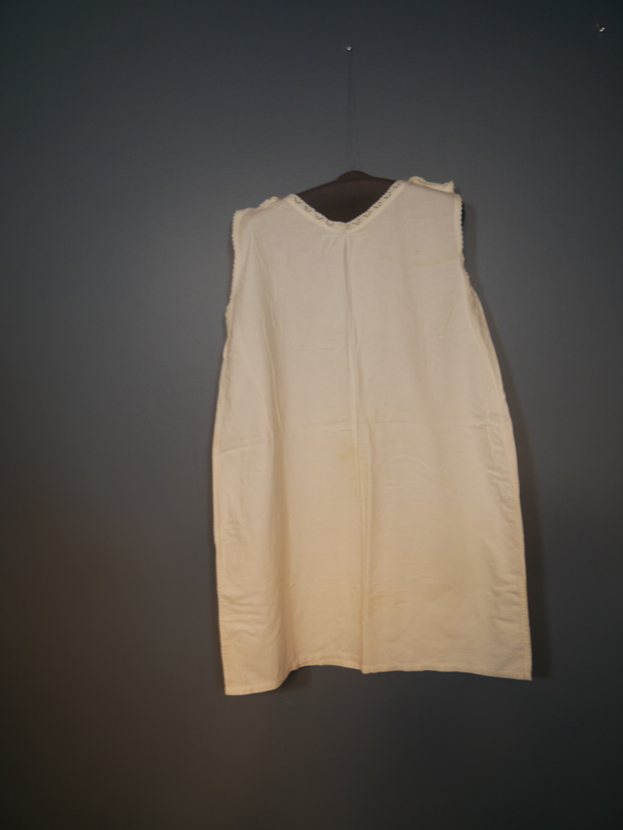 Hvit underkjole i bomull. Blondekanter rundt ermene og halsen. Festet med en knapp på hver skulder.
