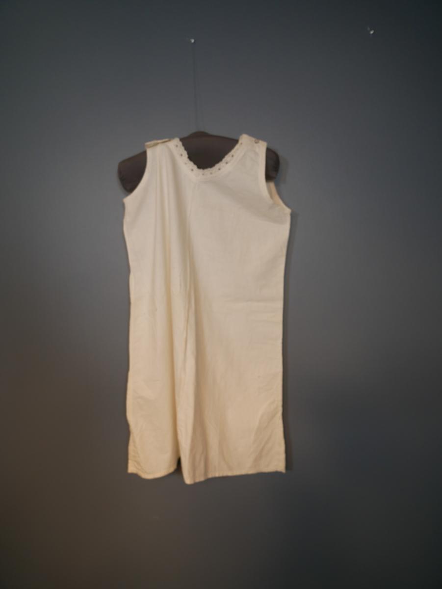 Hvit underkjole i bomull. Rundt halsen er det et hvitt blondebånd. På venstre skulder er det en knapp. På høyre skulder er det ett knappehullt, knappen mangler.