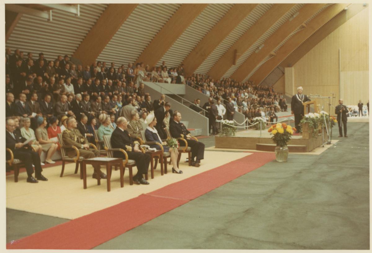 Fra åpningen av Mossehallen.  Bilde 1: Kong Olav V ankommer til Honnørbryggen i Kanalen.  Bilde 2: Fra Mossehallen, åpningsseremoni, ordfører Emil Andersen taler. Kongen og kronprinsparet sitter i første rekke.