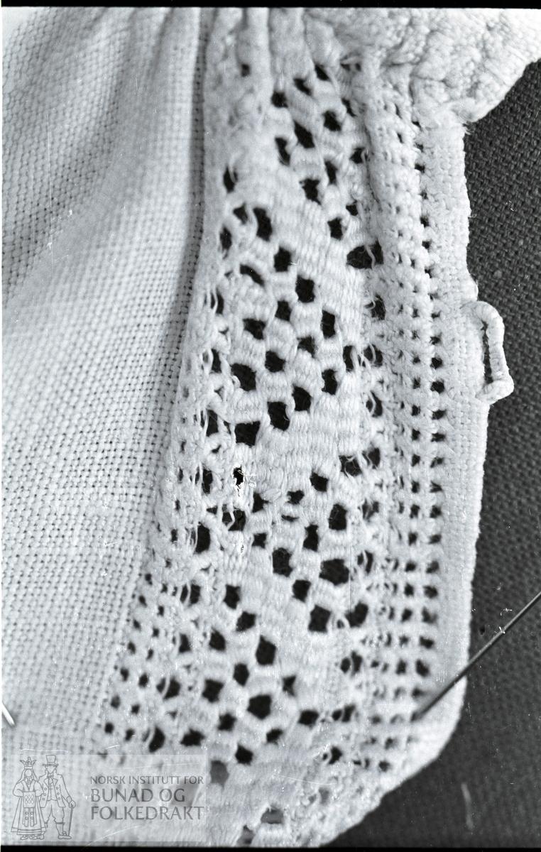 Nordhordlandsmessa nr. 50.  -  Heimevoven lin.  Open under erme, ikkje ermespjell.  Trekanta lask på skuldrene, til halslinninga.  Breidde halslinning:  3,7 cm, breidde stolpe:  3 cm, breidde ermelinning:  2,1 cm.  (Kort a-b).