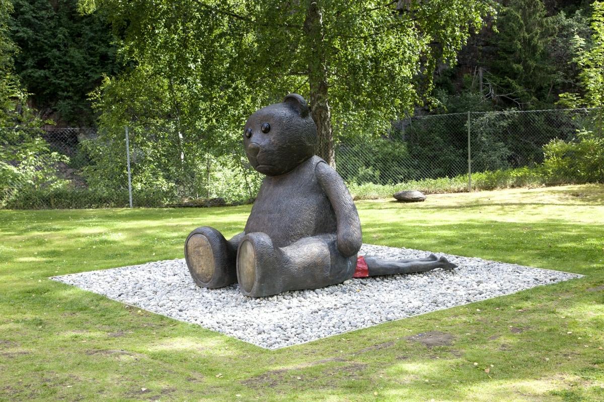 Stor teddybjørn som sitter på en person.