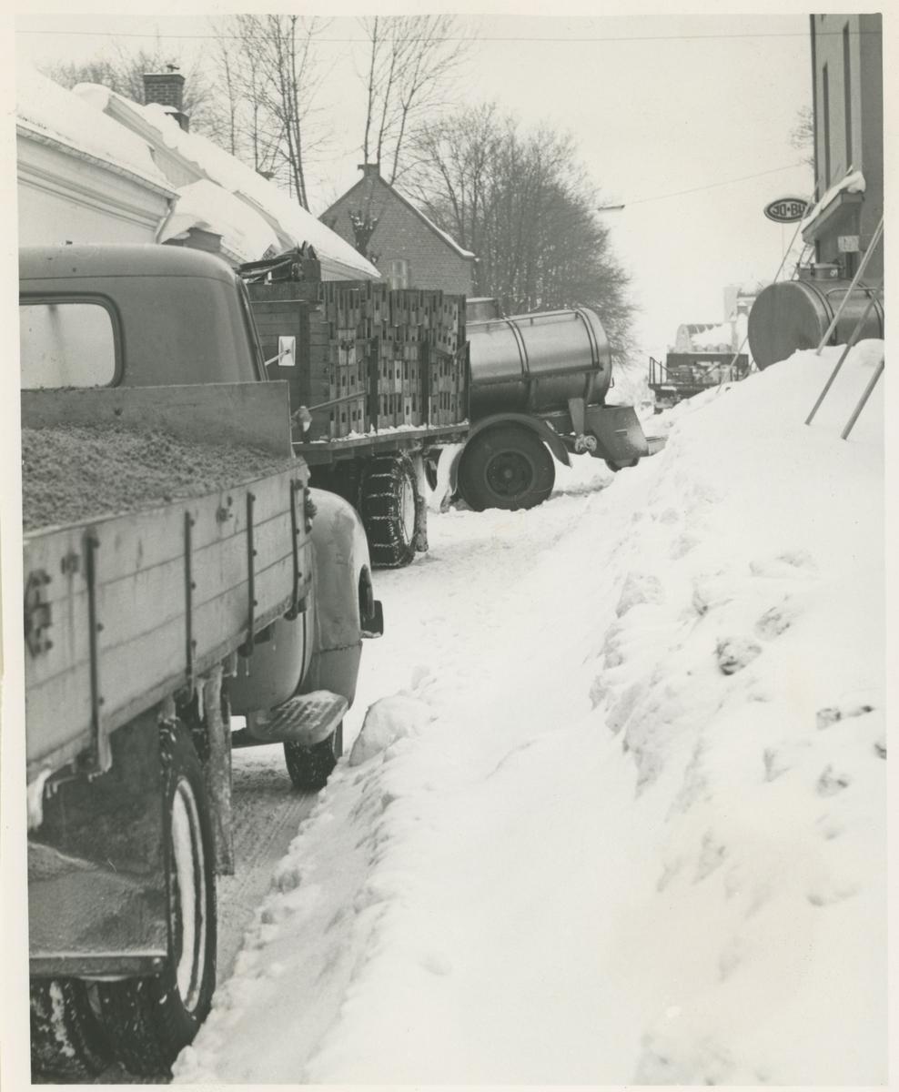 "To vinterbilder:  1:Snørydding i Værlegata. Midt i bildet ""Beck-gården"".  2: Dronningen gate, Idrettens hus til høyre."