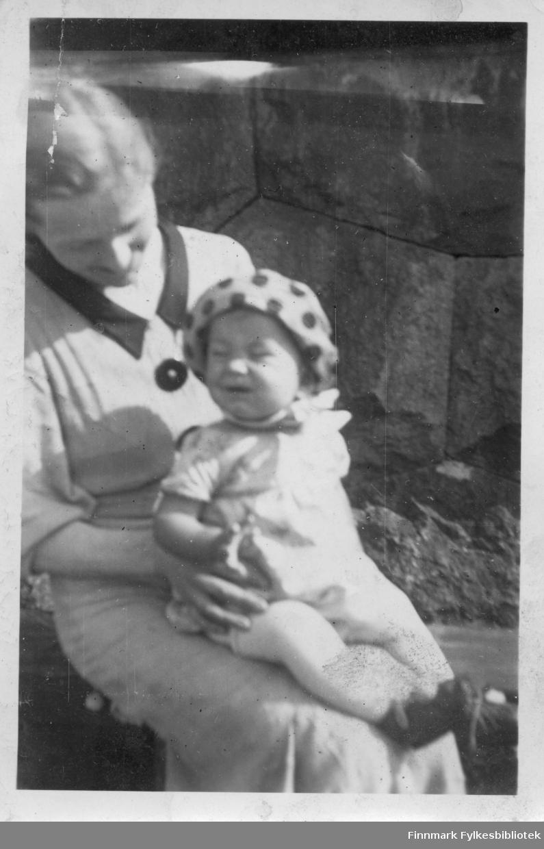 """Mor og barn. Bak bildet tekst på finsk: """"Ei minua itketä"""", som betyder """"neida, jeg gråter ikke""""."""