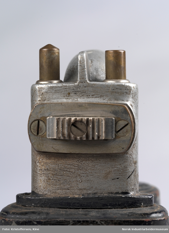 Signallykt med batteri brukt av skiftepersonell ved Norsk Transportaktieselskab/Hydro Transport i Tinn. Lykten har håndtak til å bære i, og et rom for batteri på baksiden. I front ved håndtak er to knapper, brukt for å skifte mellom rødt og grønt glass. Den ene knappen har en flat topp, mens den andre knappen er litt høyere og har en spiss topp. Knappene er utformet forskjellig for å kjenne med fingeren hvilken glasskive som var nede. Den spisse knotten ga rødt lys. I front er et stort buet glass under logo og en skrue. Det kan tenkes at skruen brukes for å åpne opp for tilgang til batteri og innmat. Under håndtak er det to mindre knapper.