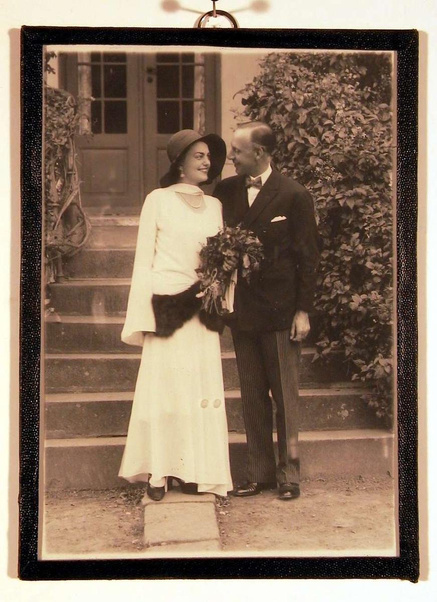 Brudebilde tatt foran trapp til sommerbolig. Brudeparet ser på hverandre.