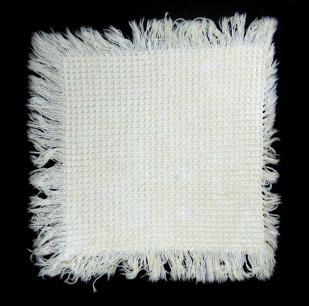 Vevd brikke i bomull med frynser. Brikken har vaffelstruktur. Den er håndvevet av løstvunnet garn.