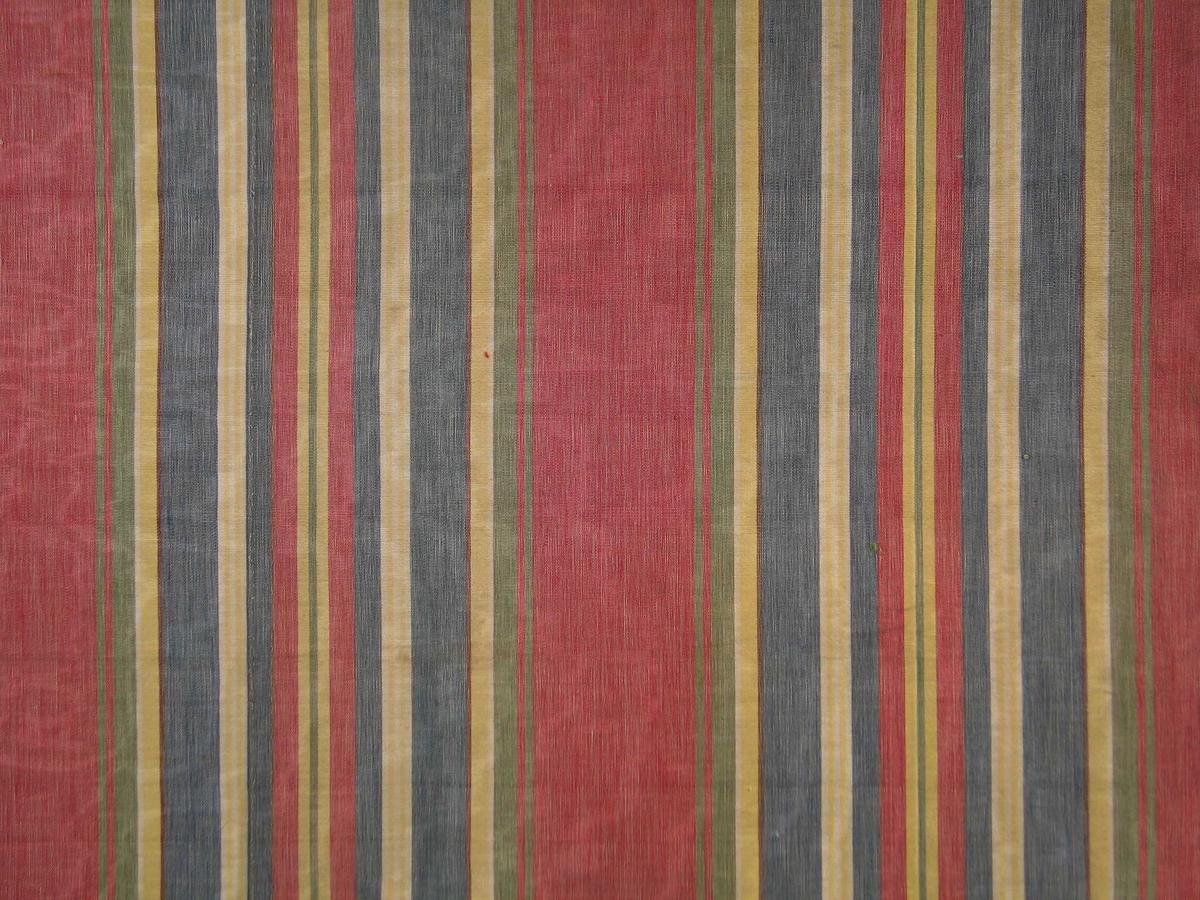 Rest av stripete bomullsstoff i fargene rødt, gult, grått, hvitt, gulgrønt og brunt. Striper i ulike bredder, rapport 32,4. Vevbredden er 131 cm. Mercerisert renning.
