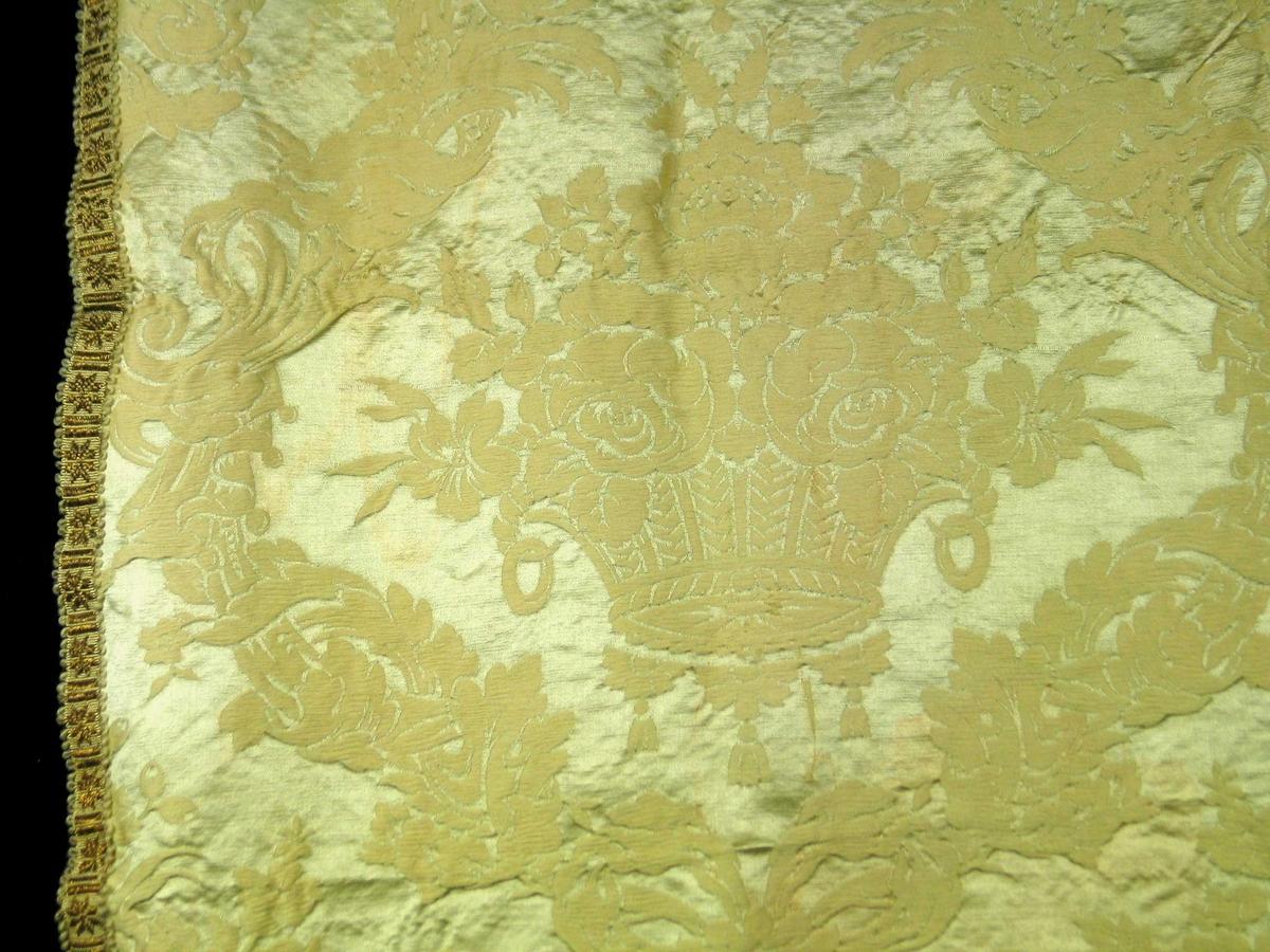 Gulgrå portiere i jacquardvevd damask. Materialet er kunstsilke med blank renning og matt innslag. (Glatt kunstsilke, senere benevnet rayon) Wienerfalder er lagt med isying av ringer. Kantebånd av metall i ene siden og nederst. En mønsterrapport har h: 57 og br: 63. Sterkt svungne guirlandere av fortegnet bladverk, bundet sammen med sløyfe. Midtpartier mellom guirlandere: kurv fylt med to roser og andre blomster.