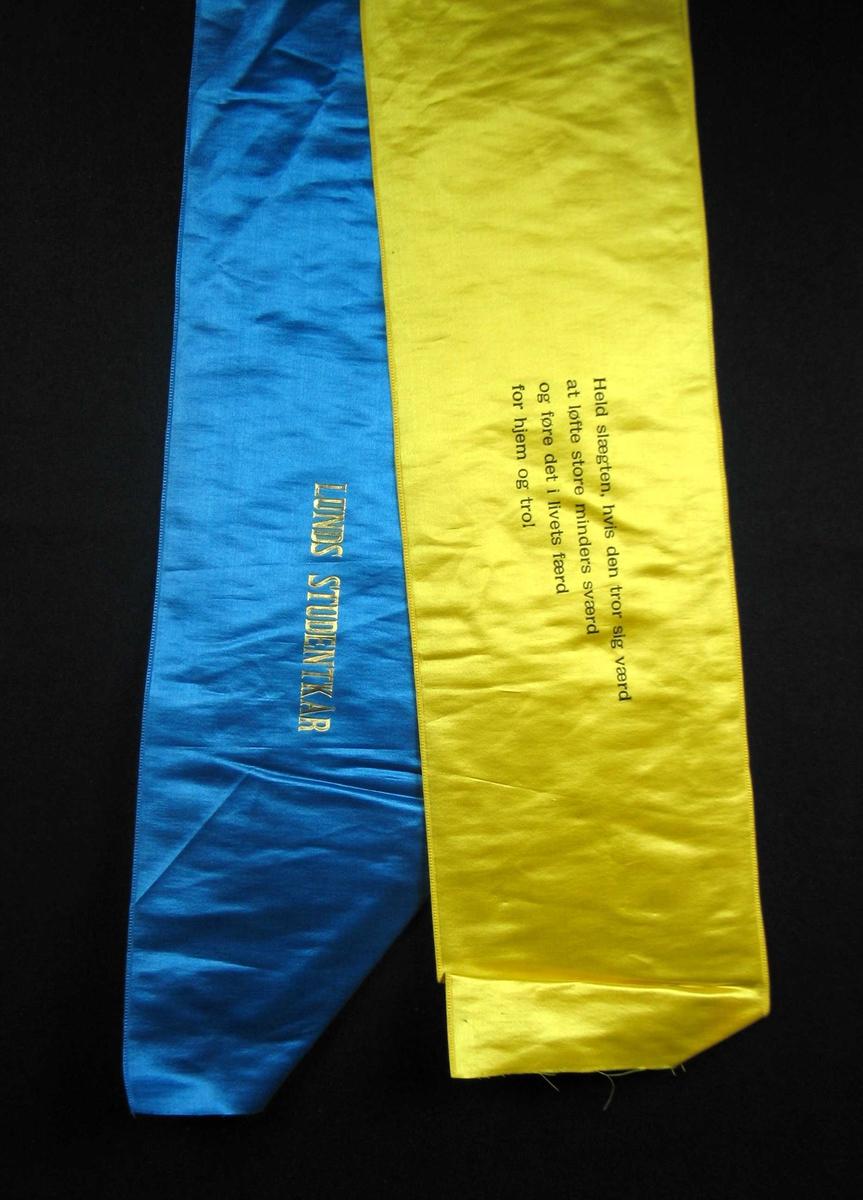 Begravelsessløyfe i blå og gul silke med tekst i svart og gull.
