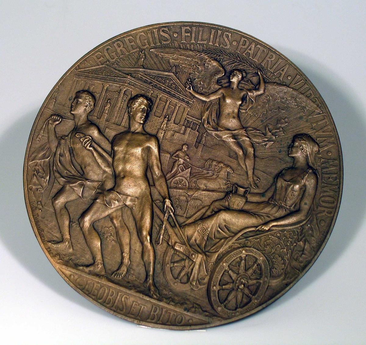 Rundt bronserelieff som forestiller Cleobis et Bito. Hempe bak.