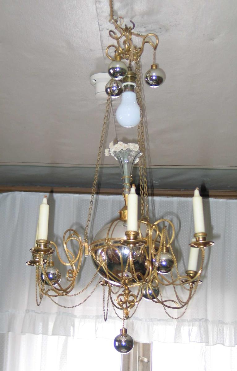 Lysekrone i metall med seks lysarmer til stearinlys. Lysekronen er dekorert med kjeder og kuler. I midten er det festet en slipt traktformet blomstervase i glass. Elektrisk lys montert i toppen.