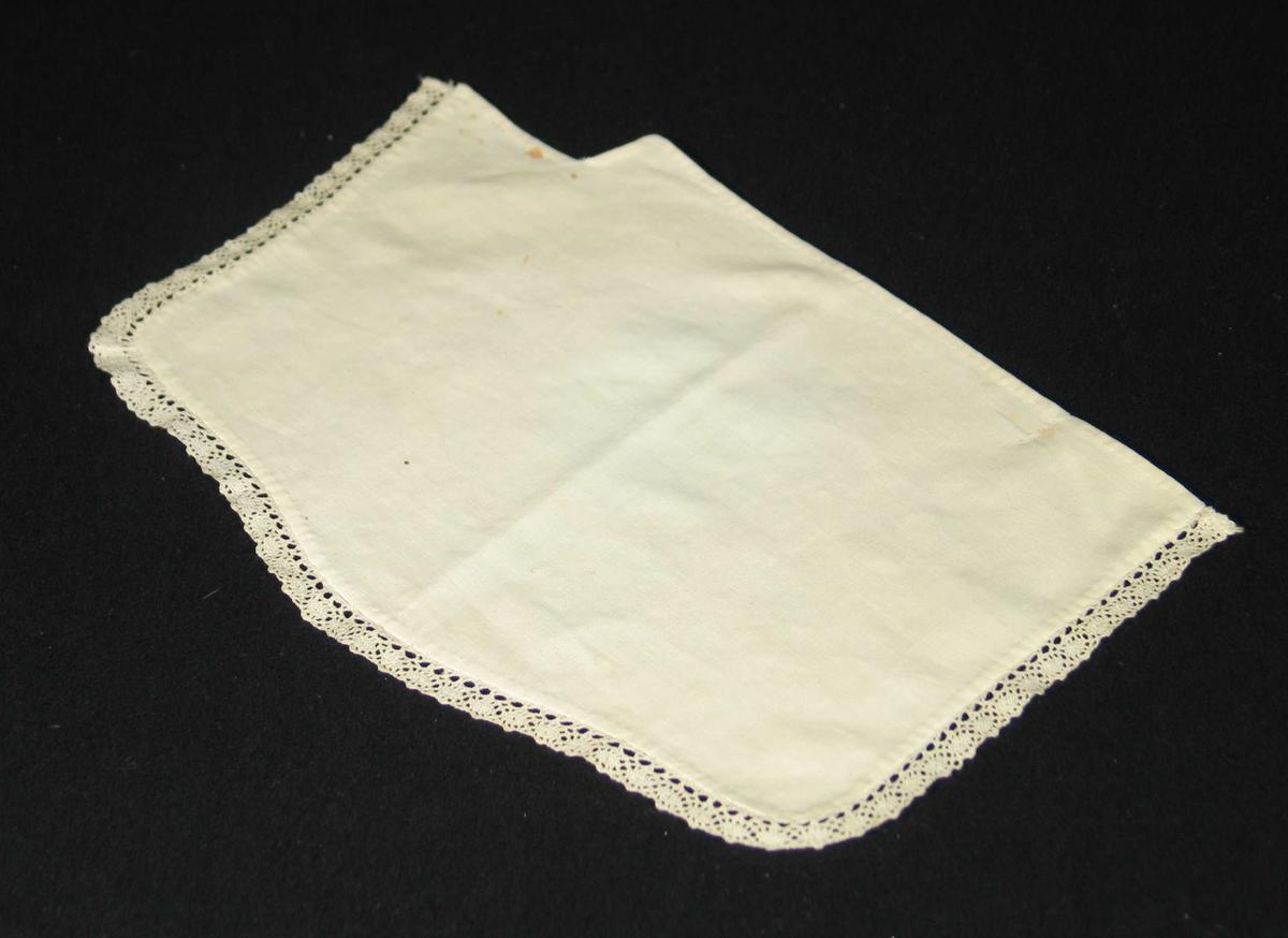 Hvit serviett i bomull kantet med blonde på tre sider. Den er sydd etter formen på hylla.
