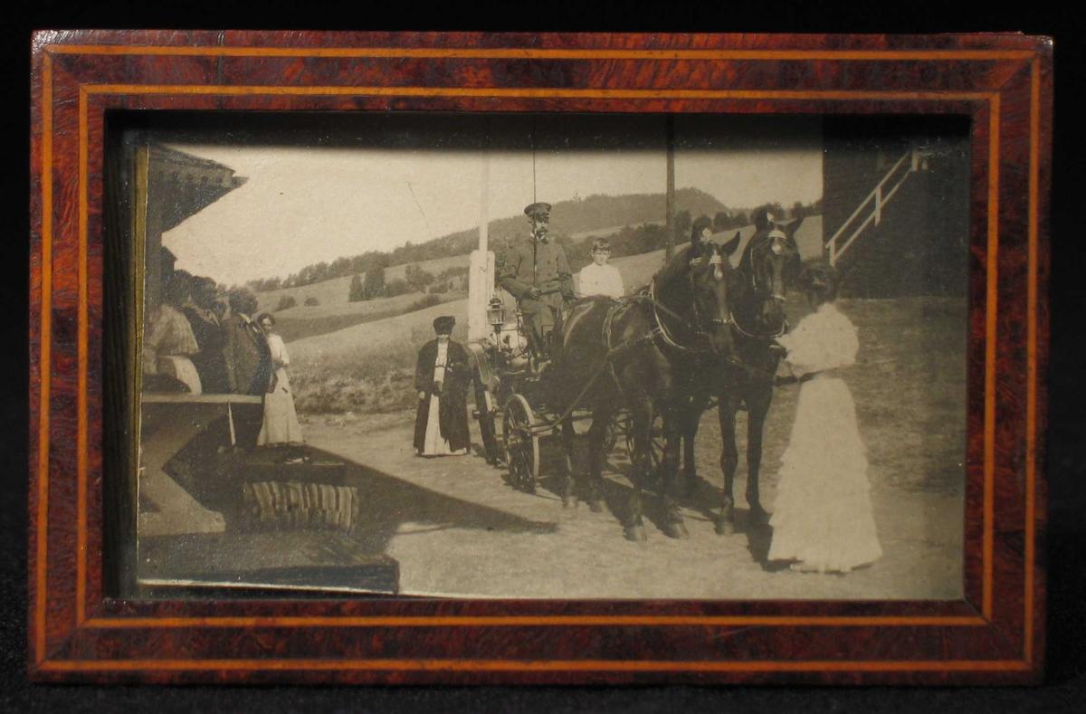 Kusk med to hester og vogn i tunet. Skuelystne på trappa.