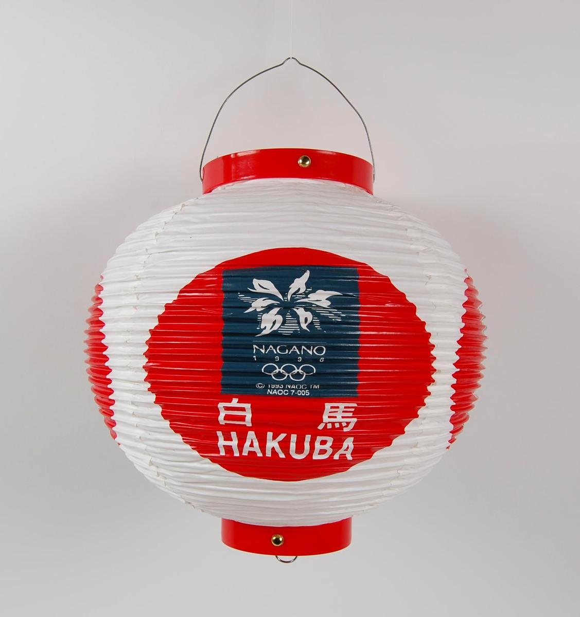 Rund lykt med logo for Paralympics i Nagano i 1998 og de olympiske vinterleker i Nagano i 1998. Lykta kan foldes sammen.