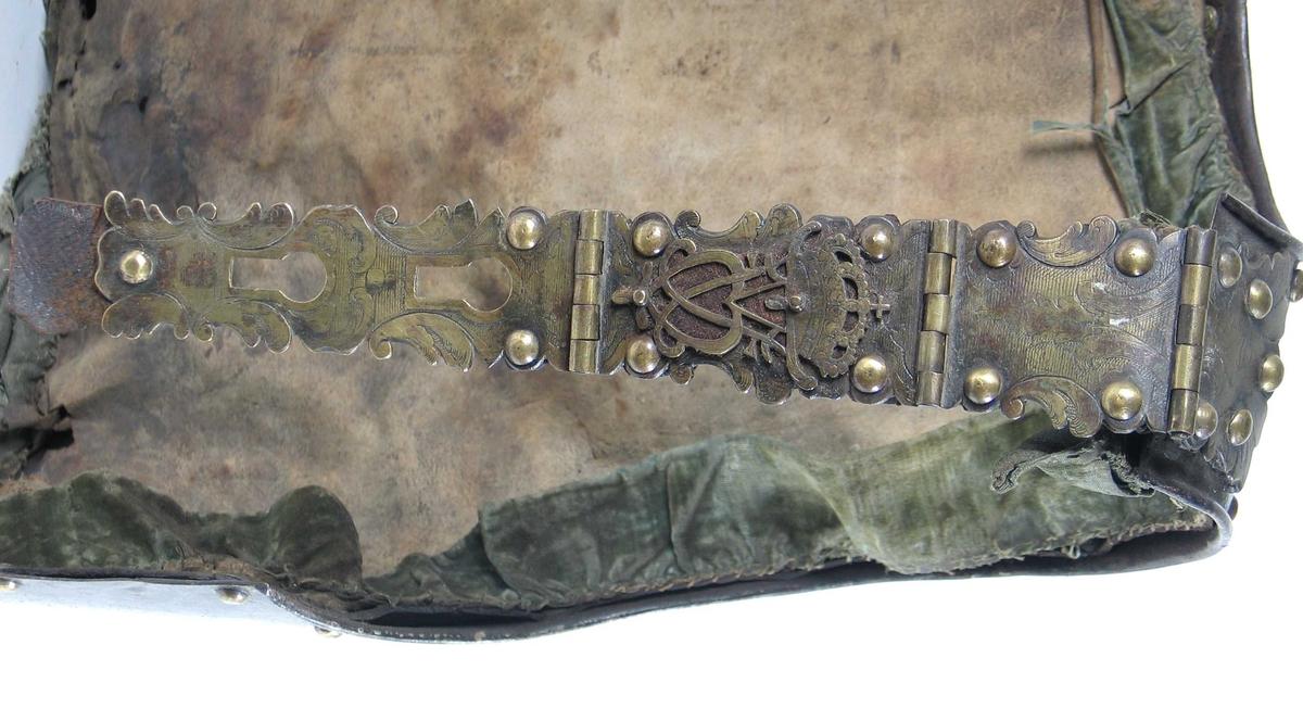 Dansk-norsk ryggtplate fra 1762 med to messing skulderremmer med F5 kronet speilmonogram. Akantus og strekdekor. Messing nitter langs kantene.  Ryggen har orginalt for med grønne velurkanter. Smal nedre kant.