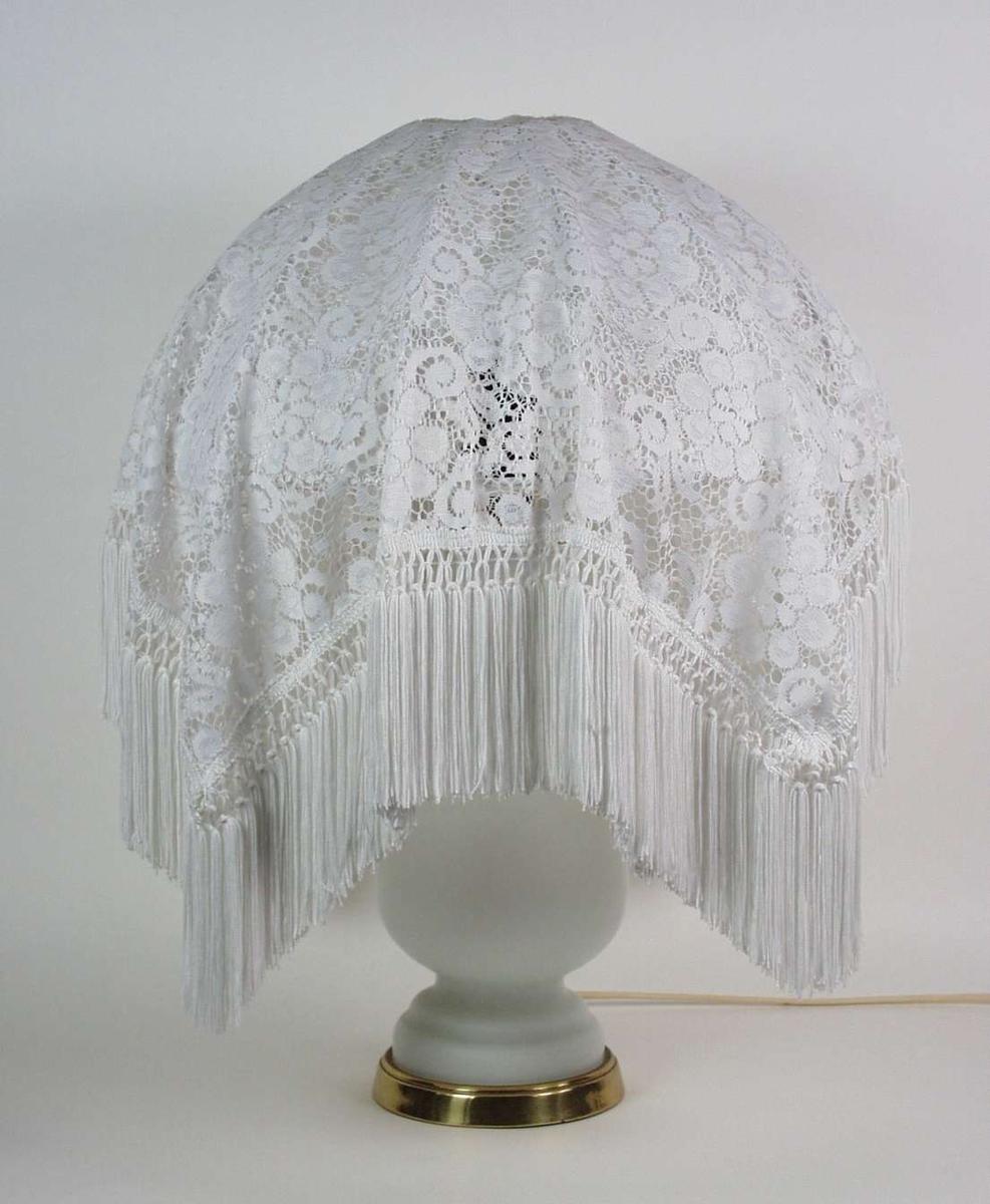 Bordlampe med hvit sokkel i opalin med metallring nederst. Skjermen er trukket i hvitt gjennombrutt stoff med frynser.