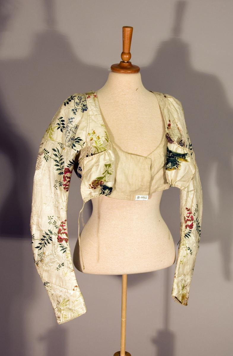 Håndsydd empire kjoleliv av hvit brosjert silke med blomstermønster. Livet har et godt snitt med smale skulderstykker og stor armringing foran og bak. Alle stykkene har skjøter.  Slindret snor av naturfarget lin i løpegang midt foran i halsringingen og under bysten. På bakstykket på ermene er det spor av at kjolelivet er omsydd. Ermene har splitt ( 6 cm) nederst. Midt bak er spor etter sammensying, håndsøm med lintråd, kanskje med skjørtet?
