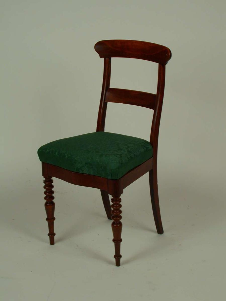 Brunbeiset stol med stoppet sete. Stoffet i setet er grønt.  Stilen er en blanding av biedermeier og historisme.
