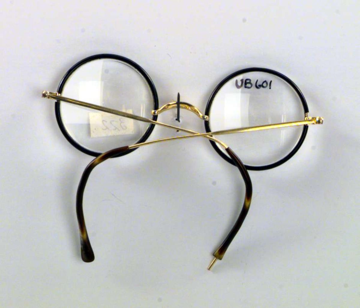 Briller med sirkelrunde glass. Brillene er av gulll. Innfatningen er brun. Brillene har ikke nesebeskyttere.