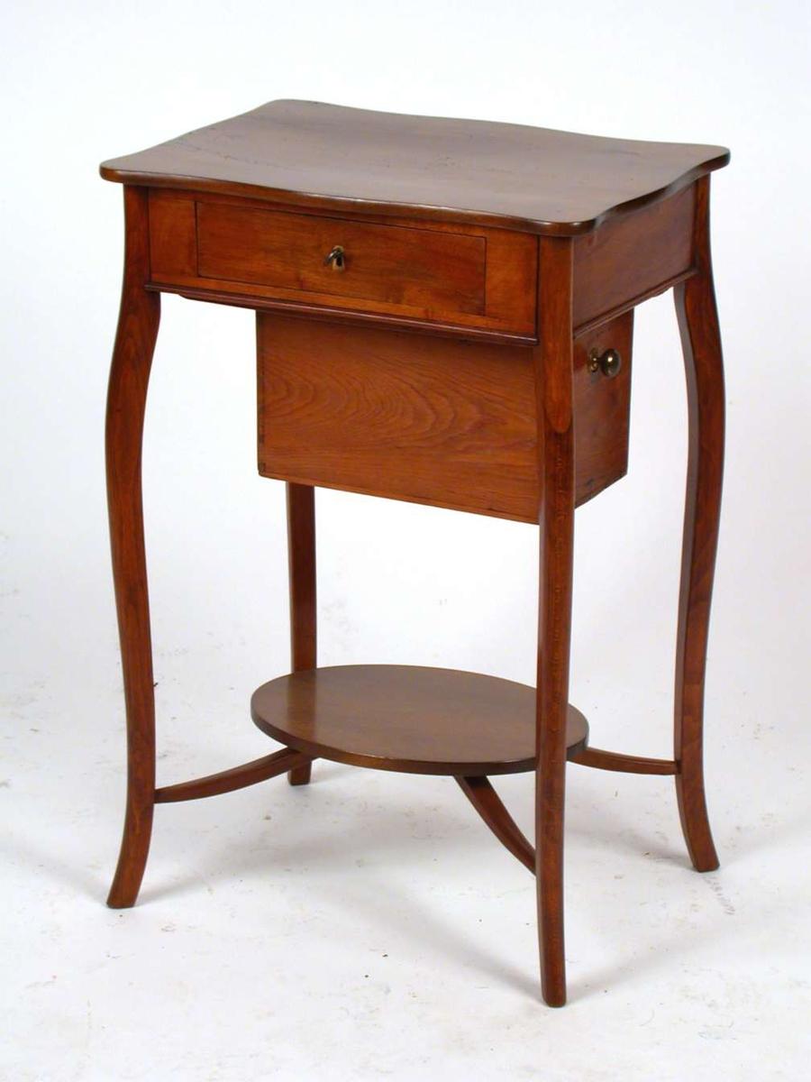 Sybord med to skuffer. Den ene skuffen er festet under selve bordet. Bordplaten har en buet linje.