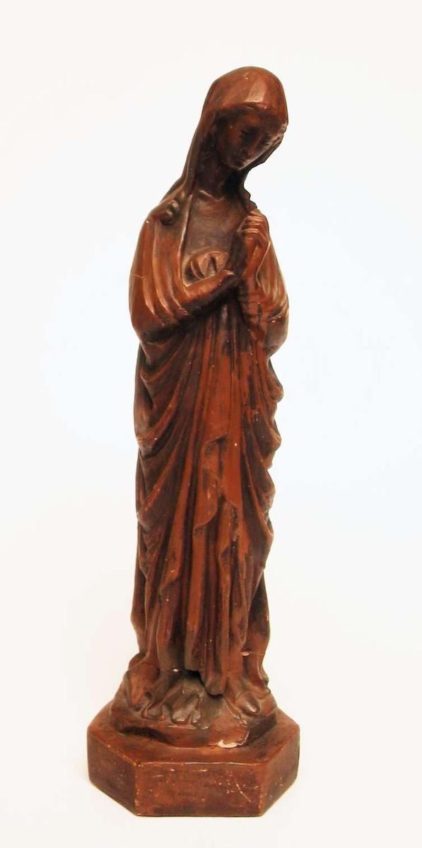 En skulptur av jomfru Maria støpt i gips og malt brun. Skulpturen har vært slått i to og er limt sammen igjen.