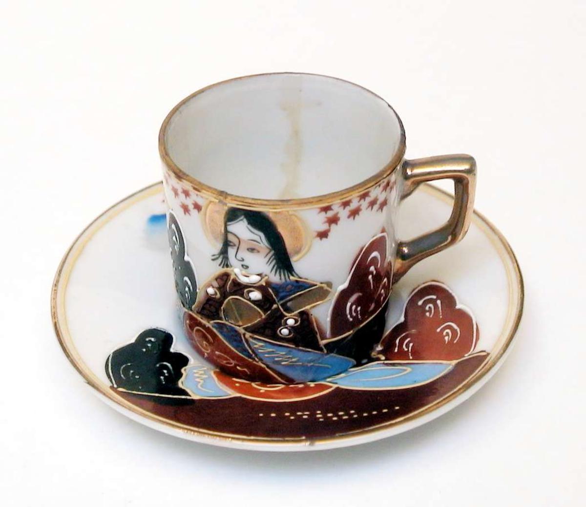 Mokkakopp med skål av hvit porselen. Både kopp og skål har håndmalt dekor. Motivet er japansk. Kanten på koppen og skålen er forgylt, likeså hanken. Koppen er limt.