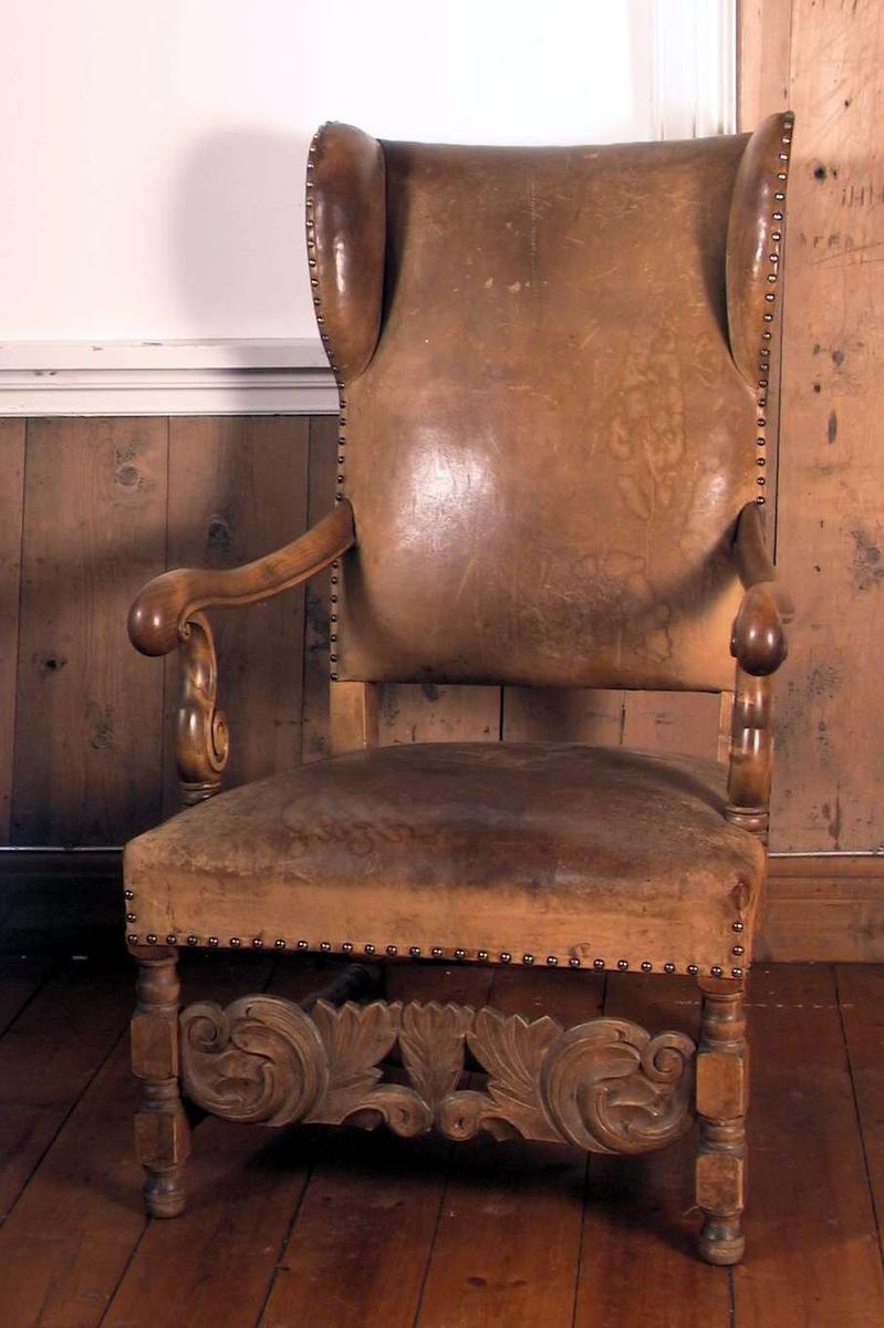Ørelappstol i barokk stil. Polstret sete og rygg dekket med lær. Svungne armlener. Rikt utskåret bindingsbrett mellom forbena.