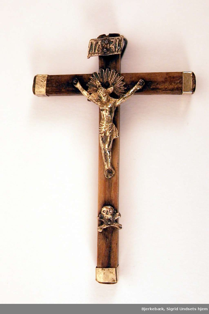 Kors av tre, med endebeslag i messing. Kristusfigur og dødningehode er i støpt messing. Over kristusfiguren en messingplate med bokstavene I N R I. Oppheng i metall på baksiden.