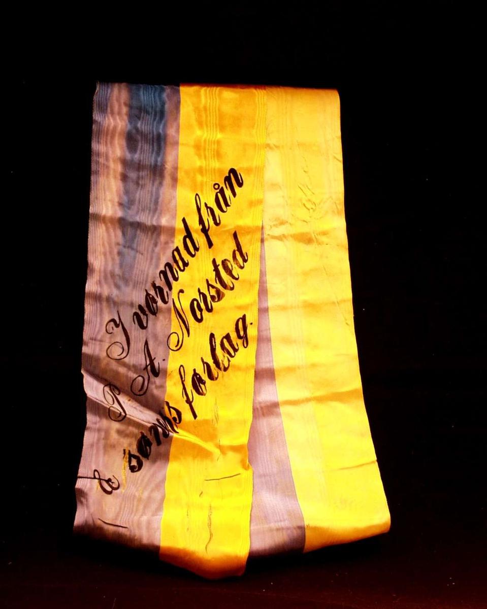 Bånd i gul og blå silke. Båndet er delt i to. På båndet står det: I vørnad från P. A. Norsted & søners førlag.