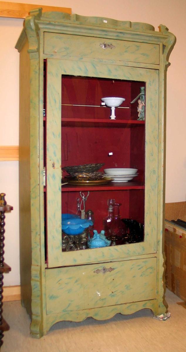 Skap med 2 skuffer og en skapseksjon med tre hyller. Det er glass i døren i skapseksjonen. Skapet er marmorert i grønt og blått. Innvendig er skapet malt rødt. Skuffene har beslag i tinn eller sink. Et av beslagene er defekt.