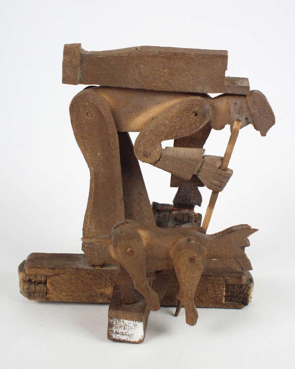 Leken består av en mann og en hund i tre plassert på en trefot formet i kors. Mannen bærer diverse redskap.