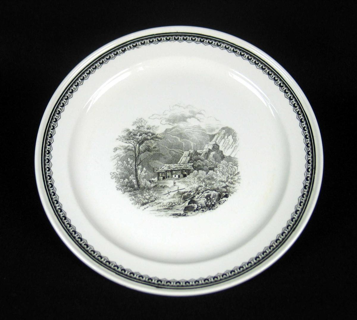 Middagstallerken i benhvit keramikk med sort dekor.