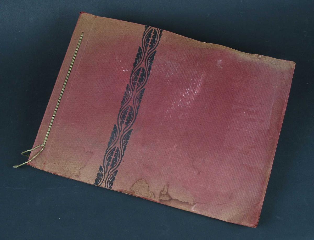 Fotoalbum i rød kartong med svart mønsterbord på omslaget. Sidene er av gråbrun kartong. I ryggen er det en grønn tvinnet snor.