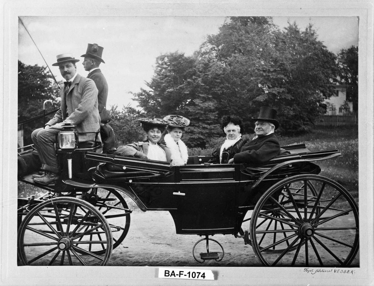 Fire personer anføttes i hestetrukket vogn, to menn på kuskesetet (ene kusk)
