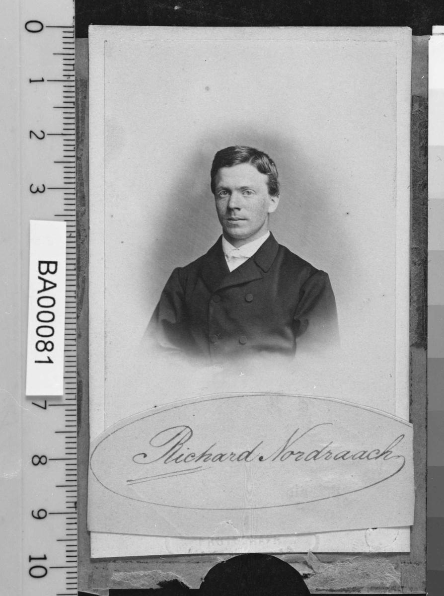 Portrett av ung mann i mørk jakke med hvit skjorte.