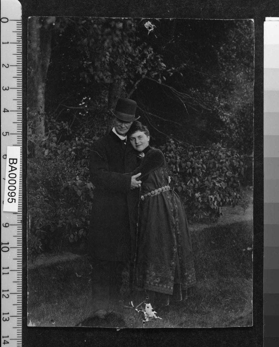Utendørsfotografi av en mann og en kvinne med armene om hverandre. Han i mørk dress, hatt og frakk og stokk; hun i mørk bunad med sølvbelte og smykker. Hun ser direkte på betrakteren.