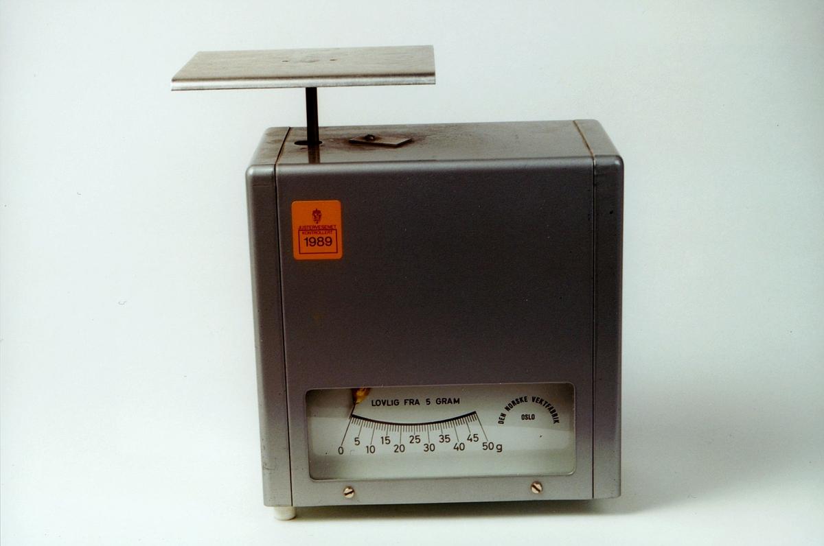 Skala fra 0-50 g. Lovlig fra 5 g på skalaen. Bak på maskinen står det: Justert for fraktberegning. Lovlig fra 5 g. 3 årlig revisjonsplikt. På eget skilt bak: Ikke revisjonspliktig Justervesenet
