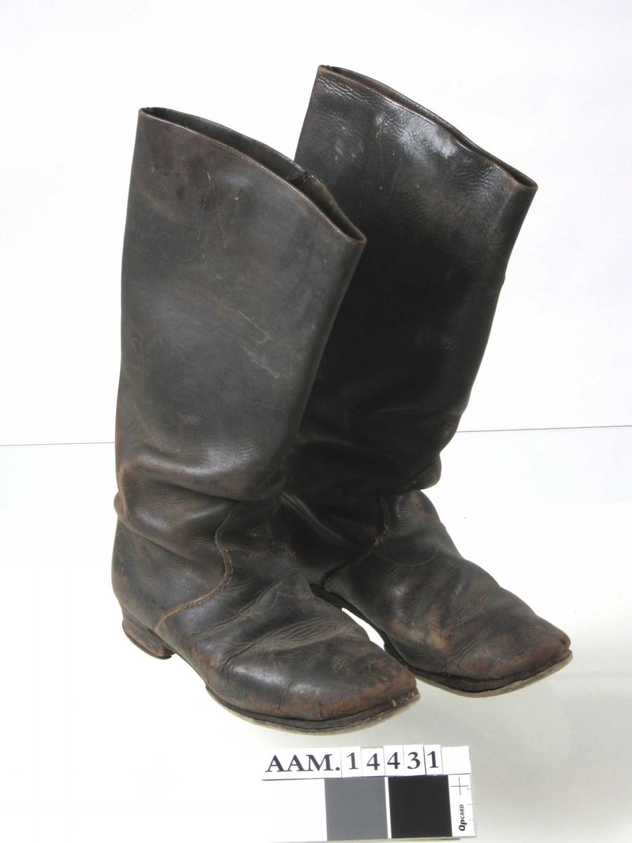 I par sorte skaftestøvler med Overlær som  går i en U form over anklene.  Nyere lys såle, slitte helflikker med  heljern langs kanten. Innvendig  to stropper sydd fast med en N formet søm.  Tilstand. endel stive, ellers gode.