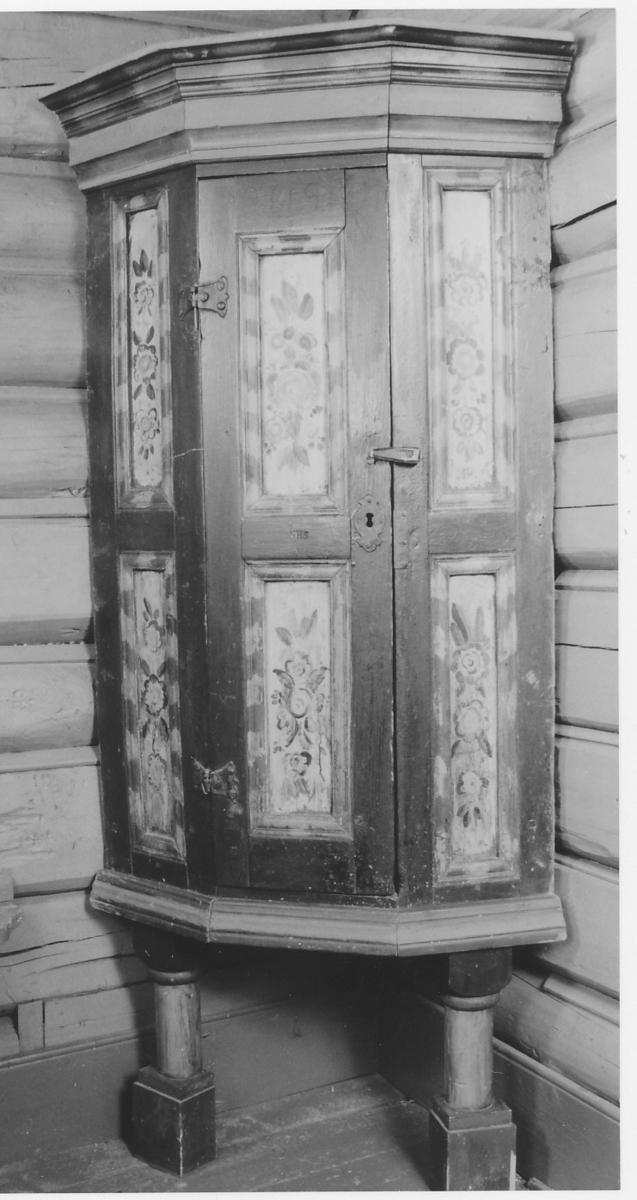 Rette sider, profilert, fremspringende krone, 1 dør med konturerte beslag, på dør og sider 2 rektangulære fyllinger over hverandre.