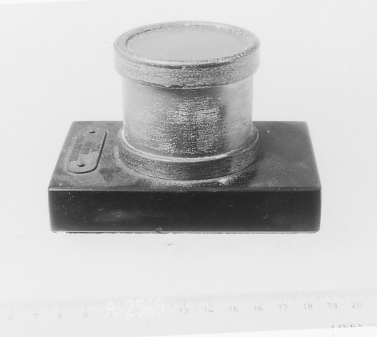 Rektangulær plate, øverst en sylinder med messingbånd oppe og nede, på oversiden glass over stykke av kabel med kobberledere.