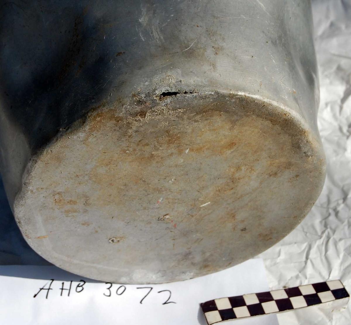 Bøtte i aluminium med stålhank. Trolig produsert som melkebøtte. Sist brukt som askebøtte. Asken har tæret hull i bunnen av bøtta.
