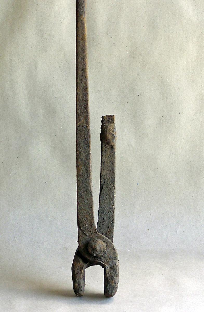 Tang med lange armer og kort kjeft. Kjeften fastrustet. Den ene armen er brukket og den andre er forlenget/essesveiset 2 - muligens 3 - steder.